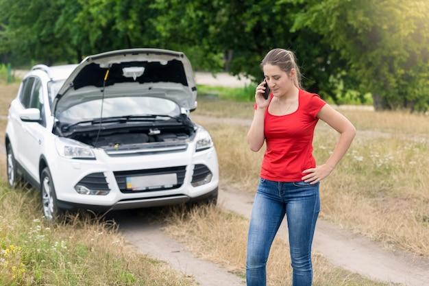 Traurige frau, die am kaputten auto auf der landstraße steht und das handy um hilfe ruft