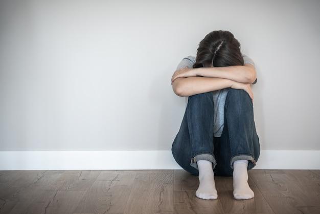 Traurige frau, die auf einem boden allein im leeren raum, in der verzweiflung und im einsamen konzept mit kopienraum sitzt
