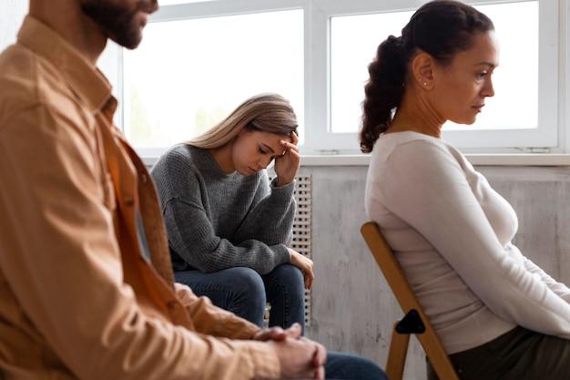 Traurige frau, die auf einem stuhl bei einer gruppentherapiesitzung sitzt