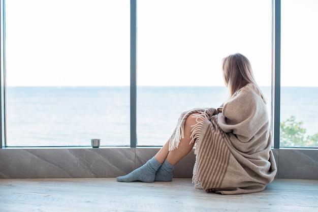Traurige frau, die auf einem warmen boden in socken eingewickelt in einer woolen decke nahe dem großen fenster im licht sitzt. herbststimmung, wärme und gemütlichkeit.