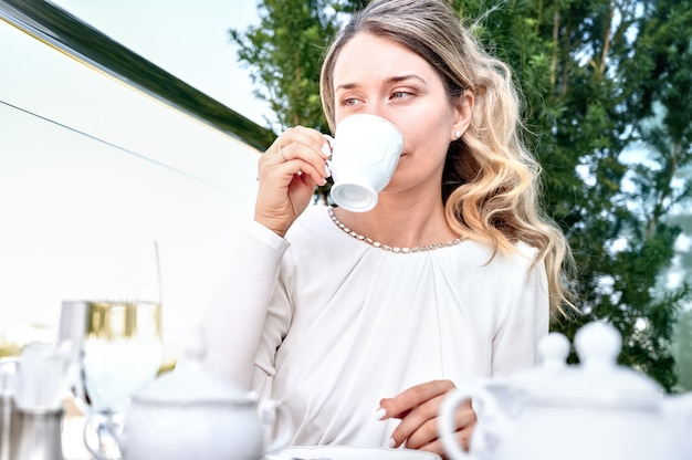 Traurige frau, die eine tasse kaffee trinkt