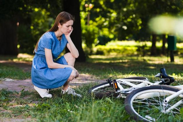 Traurige frau, die ihr fahrrad betrachtet