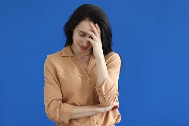 Traurige frau, die ihren kopf auf blauem hintergrund hält