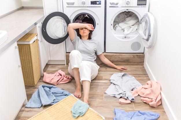 Traurige frau, die im waschsalon mit einem stapel der schmutzigen kleidung sitzt