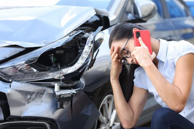 Traurige frau, die in der nähe des autofahrerkonzepts am handy spricht