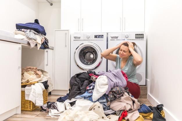 Traurige frau, die in einer waschküche sitzt
