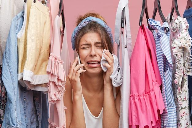 Traurige frau, die panik hat, während sie nichts zum anziehen hat, durch kleiderständer schaut, über smartphone spricht und vor unzufriedenheit weint.