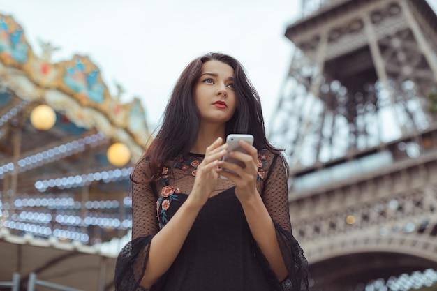 Traurige frau, die smartphone nahe dem eiffelturm und karussell, paris verwendet.