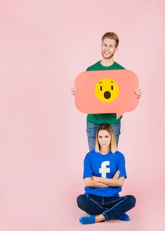 Traurige frau, die vor dem glücklichen mann hält entsetzte emoji spracheblase sitzt