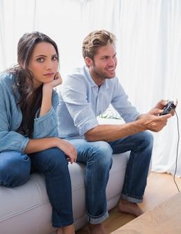 Traurige frau genervt, dass ihr partner videospiele spielt