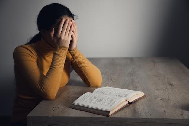 Traurige frau hand in gesicht und bibel auf tisch