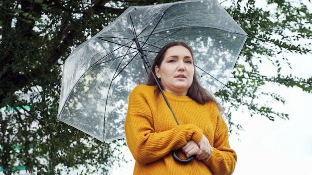 Traurige frau in einem senfpullover steht und friert bei regenwetter unter einem transparenten regenschirm.