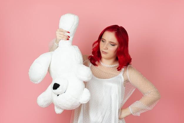Traurige frau in einem weißen kleid und mit roten haaren hält einen großen weißen teddybär kopfüber an der pfote