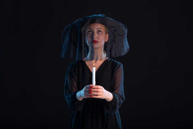 Traurige frau in schwarz gekleidet, die eine kerze auf der trauerfeier des schwarzen todes hält
