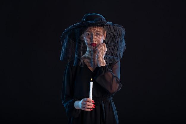 Traurige frau in schwarz gekleidet mit brennender kerze auf schwarzem trauerbegräbnistod