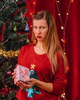 Traurige frau mit geschenk vor weihnachten