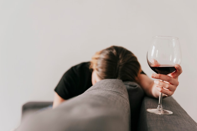 Traurige frau mit wein auf couch