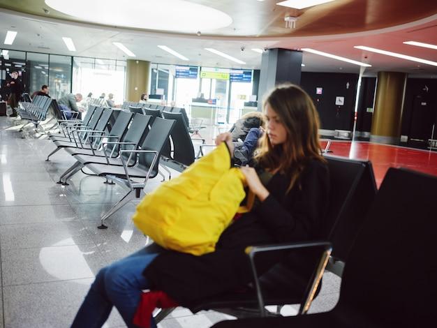 Traurige frau sitzt am flughafen mit gelbem rucksack und wartet
