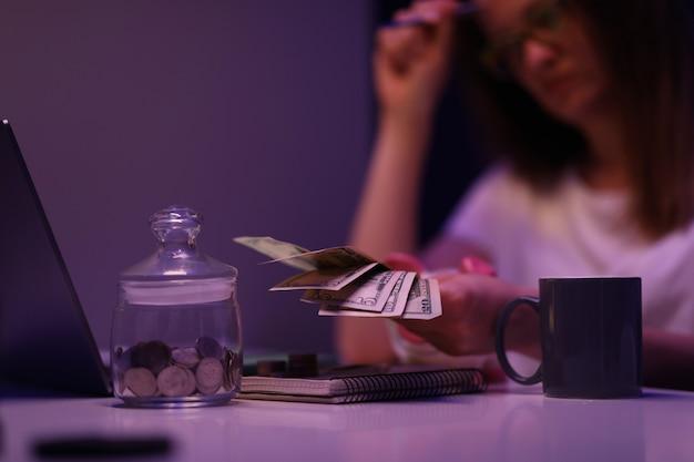 Traurige frau sitzt am tisch im dunklen raum und zählt geld für stromrechnungen nahaufnahme. wirtschaftskrisenkonzept