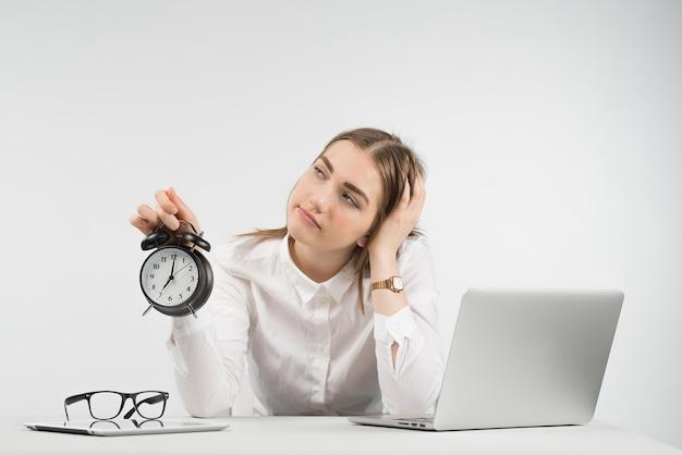 Traurige frau sitzt neben einem laptop und schaut weg, hält wecker und legt den kopf auf den arm