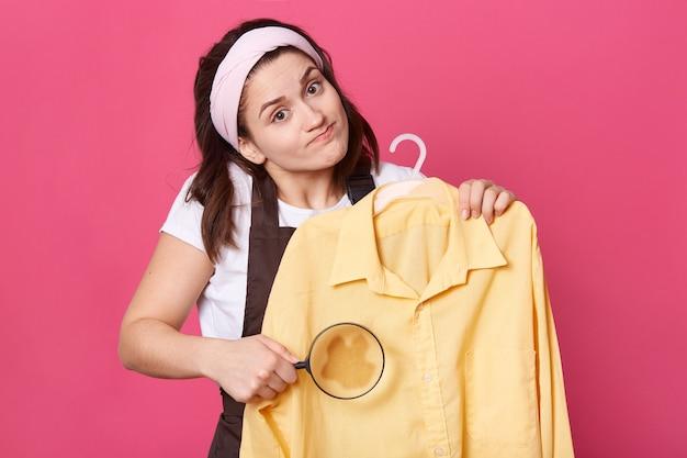 Traurige frau trägt weißes t-shirt, braune schürze und haarband, hält gelbe bluse und lupe vor große, schaut mit verwirrtem gesichtsausdruck in die kamera, weiß nicht, wie man unreinheiten entfernt.