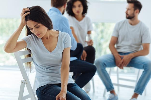 Traurige freudlose junge frau, die ihren kopf hält und sich verzweifelt fühlt, ohne zu wissen, was zu tun ist