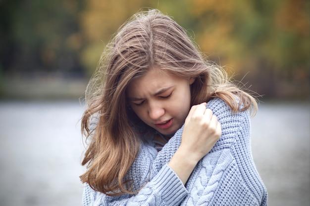 Traurige frustrierte junge frau weint, teenager-mädchen leidet unter der trennung von ihrem freund im freien im herbstpark. konzept des gebrochenen herzens. schmerz fühlen, einsamkeit.