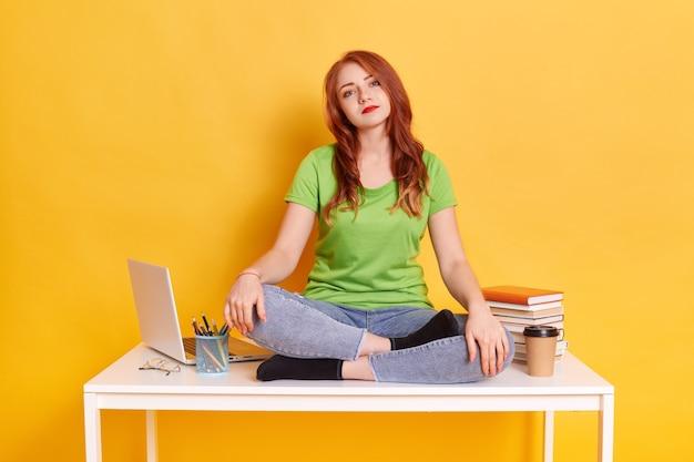 Traurige gelangweilte frau, die laptop sitzt, sitzt auf tisch mit gekreuzten beinen
