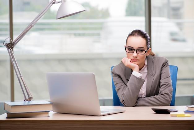 Traurige geschäftsfrau, die an ihrem schreibtisch arbeitet