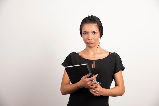 Traurige geschäftsfrau, die mit notizbuch auf weißer wand aufwirft.