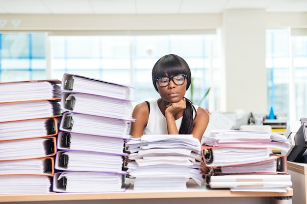 Traurige geschäftsfrau, die mit vielen arbeiten im büro am tisch sitzt