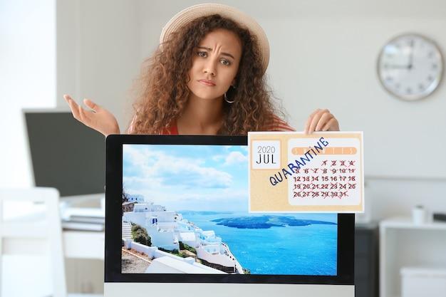 Traurige geschäftsfrau mit kalender, die während der quarantäne im büro von urlaub träumt