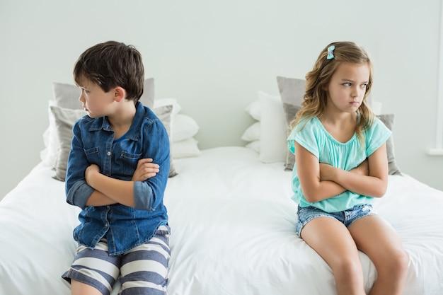 Traurige geschwister sitzen mit verschränkten armen im schlafzimmer