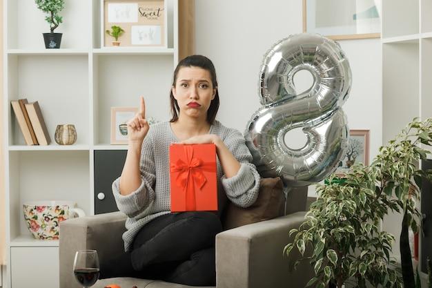 Traurige, geschwollene wangen zeigen auf ein schönes mädchen am glücklichen frauentag, der das geschenk auf dem sessel im wohnzimmer hält