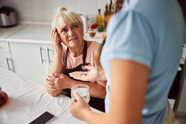 Traurige großmutter leidet unter kopfschmerzen in ihrem haus