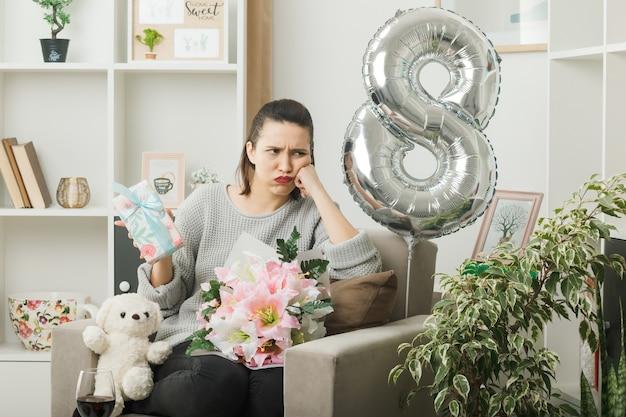 Traurige hand auf wange legen schönes mädchen am glücklichen frauentag mit geschenk auf sessel im wohnzimmer sitzend