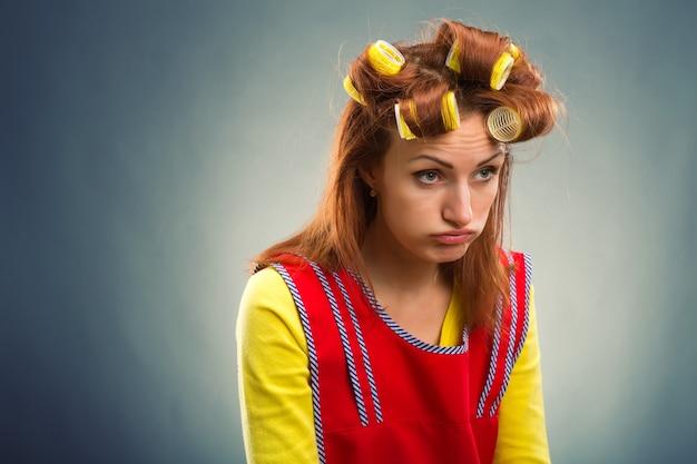 Traurige hausfrau mit lockenwicklern im haar