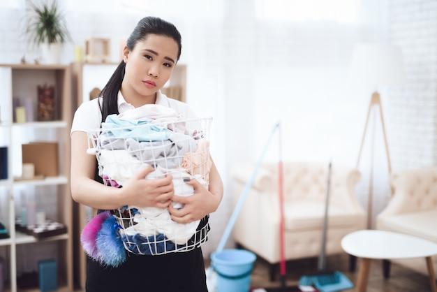 Traurige haushälterin mit überlaufendem wäschekorb