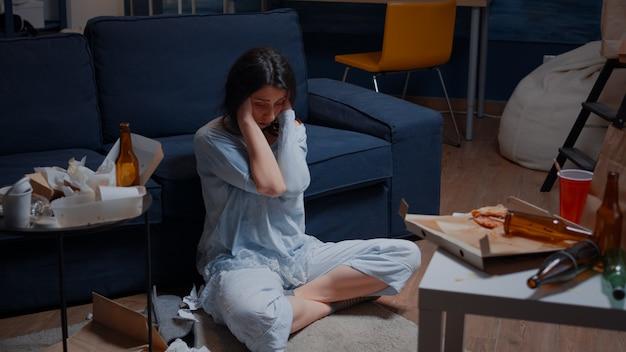 Traurige hoffnungslose junge frau, die allein zu hause sitzt und sich verzweifelt fühlt
