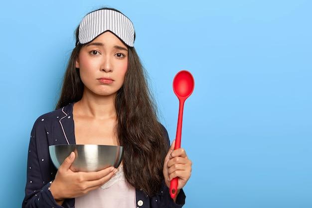 Traurige hübsche frau in nachtanzug und schlafmaske, steht früh auf, um frühstück zu machen, kocht in der küche, hält schüssel mit löffel, ist niedergeschlagen, steht drinnen