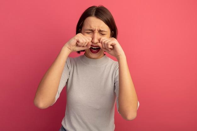 Traurige hübsche kaukasische frau gibt vor zu weinen, fäuste nah an gesicht auf rosa zu halten