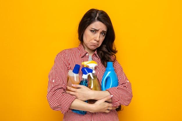 Traurige hübsche kaukasische putzfrau, die reinigungssprays und -flüssigkeiten hält