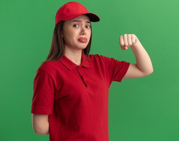 Traurige hübsche lieferfrau in uniform hält faust f