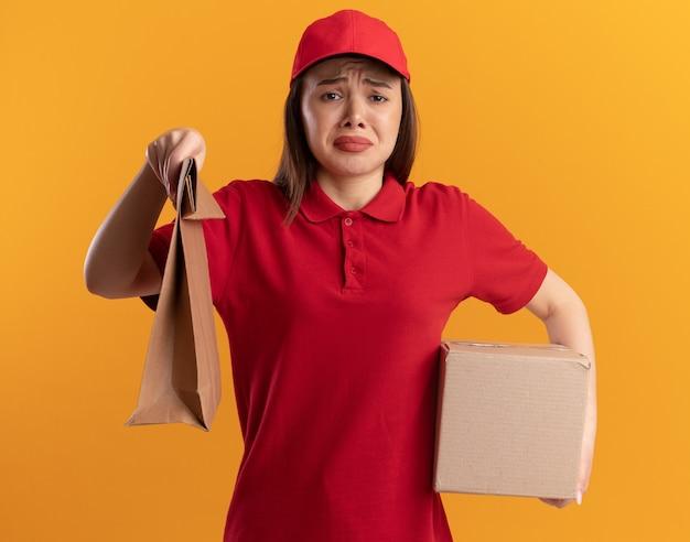 Traurige hübsche lieferfrau in uniform hält papierpaket und karton auf orange