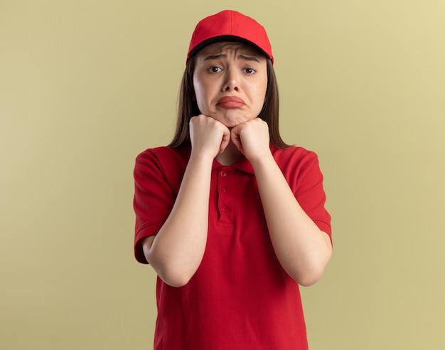Traurige hübsche lieferfrau in uniform legt fäuste aufs kinn