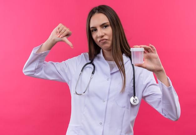 Traurige junge ärztin, die das medizinische kleid des stethoskops trägt, das leer hält, kann ihren daumen unten auf lokalisiertem rosa hintergrund