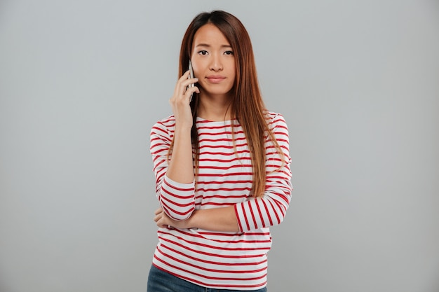 Traurige junge asiatische frau, die per telefon spricht