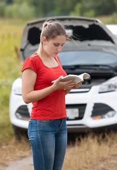 Traurige junge frau, die bedienungsanleitung am kaputten auto auf der wiese liest