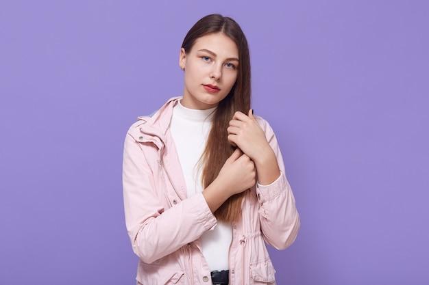 Traurige junge frau, die ihr haar berührt, während sie direkt schaut, hat gesichtsausdruck verärgert, trägt blassrosa jacke und weißen rollkragenpullover, der isoliert über lila wand steht.