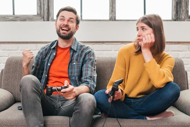 Traurige junge frau, die ihren ehemann spielt das videospiel mit steuerknüppel betrachtet